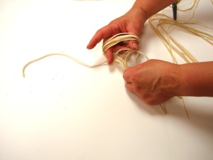 For Niqqi's hula dancer skirt, her mom makes a hoop and fishes the strands through.