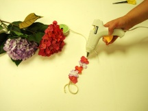 Niqqi's mom makes a lei for Niqqi by glueing some small flowers on a cord.